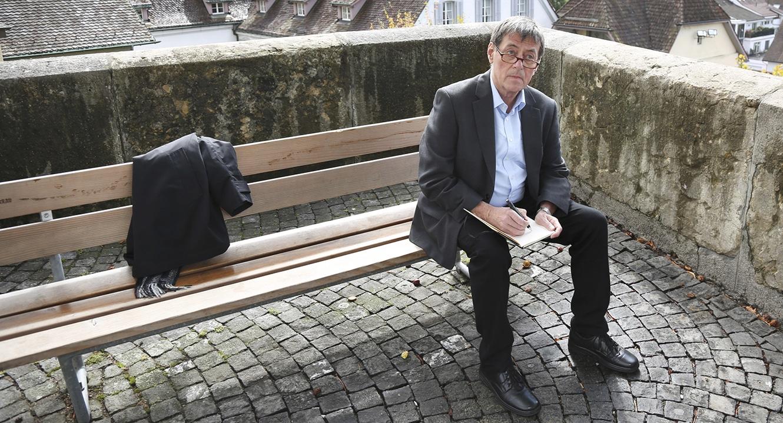 Trauerredner Jörg Bertsch sitzt auf einem Bänkli und notiert sich einige Gedanken.