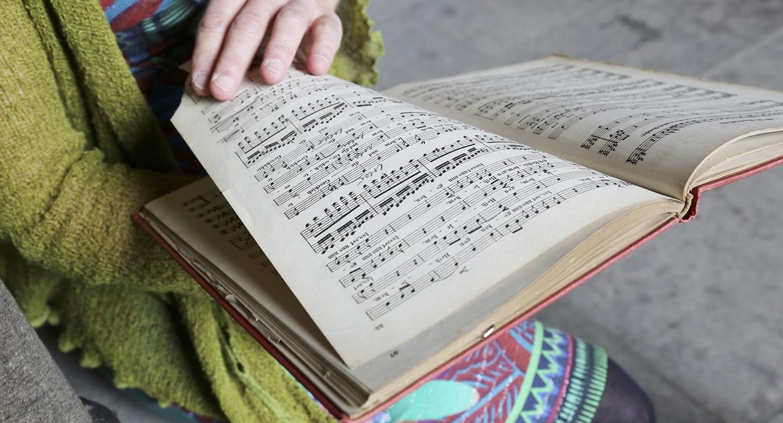 Vera Briner blättert in einem alten Gesangbuch.