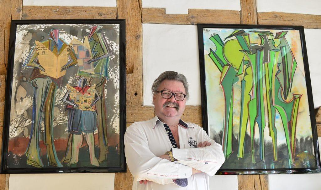 Krebsdiagnose. Peter R. Schwegler zwischen zwei Bildern seines Freundes Kurt Laurenz Metzler.
