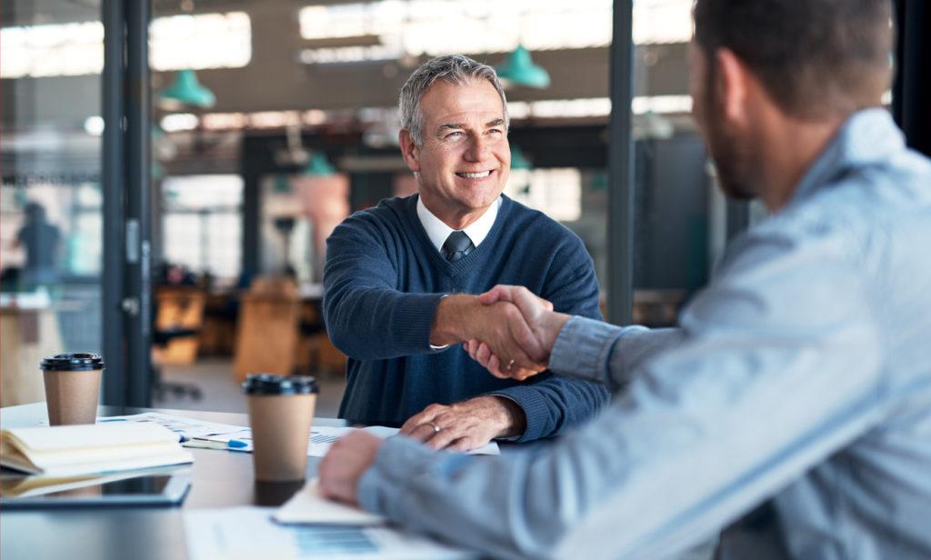 Unternehmensnachfolge: Vater und Sohn sitzen im Meetingzimmer und besprechen die Nachfolge.