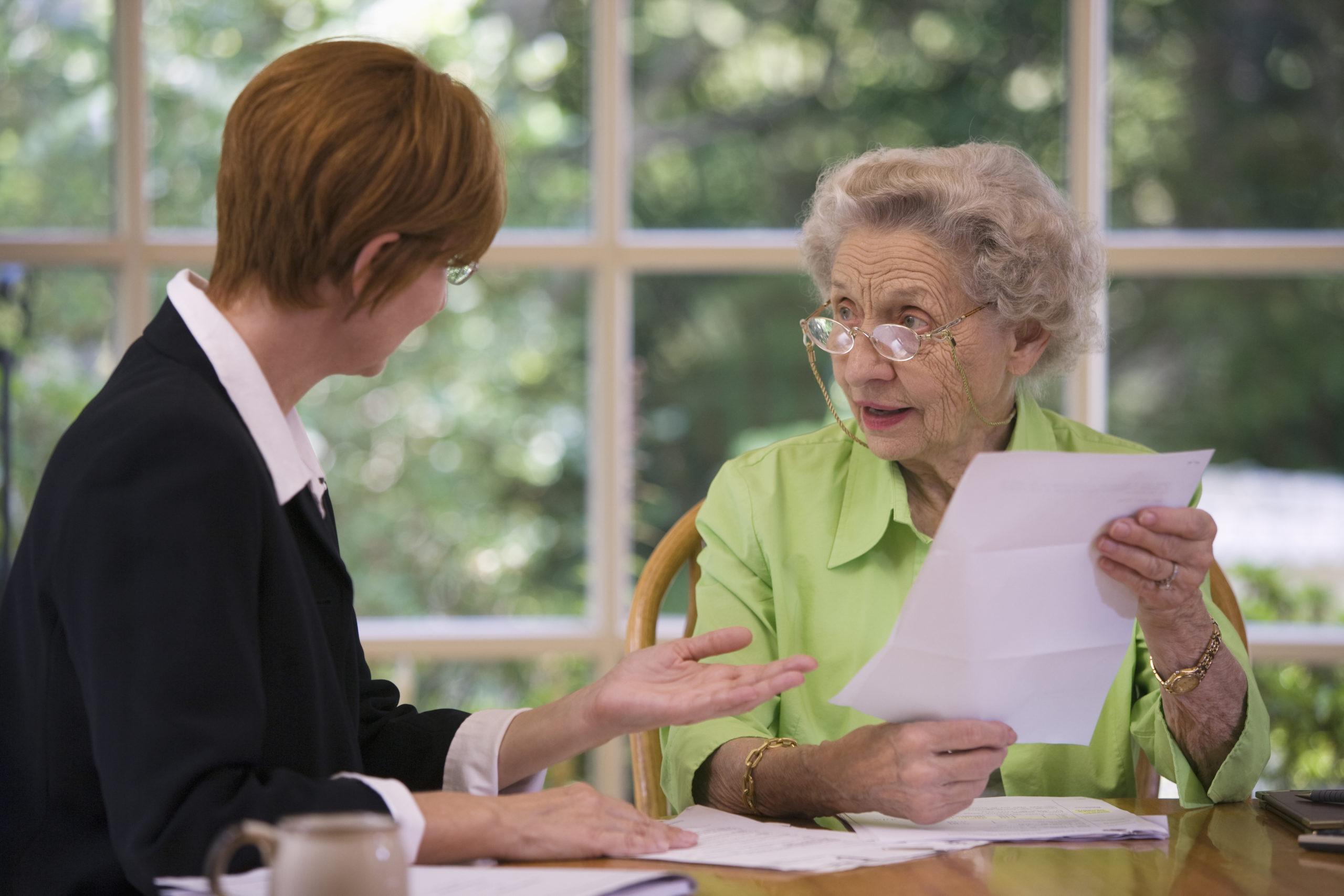 Alte Frau sitzt am Tisch und wird über den Erbverzicht beraten.
